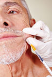 Old man getting cosmetic surgery. On corner of mouth in beauty clinic Stock Photo