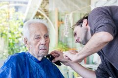 Old Man Getting His Beard Shaved By Young Skilled Man At Home Stock Photo