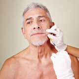 Old man getting wrinkle treatment Royalty Free Stock Photo