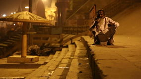 Old man at ghats of the Ganges river in Varanasi in the night time. VARANASI, INDIA - 20 FEBRUARY 2015: Old man at ghats of the Ganges river in Varanasi in the stock video