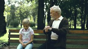 Old man gives advice to sad lonely boy who suffers from bullying at school, care stock footage