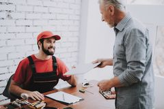 Old Man Giving Broken laptop to Worker in Workshop. Modern Workshop Concept. Manufacturing Instrument. Modern Tools Concept. Electronic Devices Concept. Mobile royalty free stock image