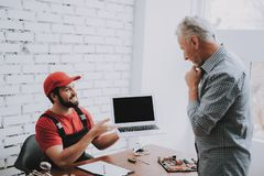 Old Man Giving Broken laptop to Worker in Workshop royalty free stock images