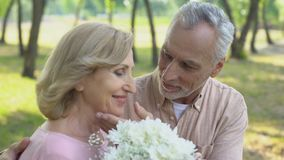Old man giving bunch of flowers to wife, celebrating marriage anniversary. Stock footage stock video