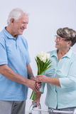 Old man giving flowers Stock Images