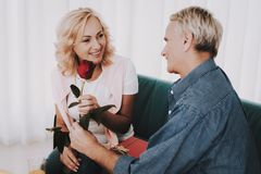 Old Man Giving Rose to Woman in Waiting Room. Red Rose in Hand. Senior Person in Airport. Tourism Concept. Old Couple in Voyage. Vacation for Pensioner. People royalty free stock photos