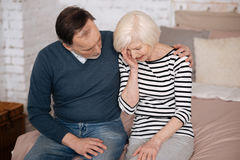 Old man giving solace to his crying wife. You can handle it. Senior men is supporting his crying wife while sitting on bed at home stock photography