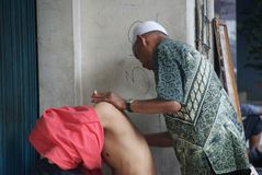Old man giving a traditional indonesian massage to a young men stock images
