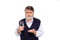 Old man with glass of water and pills in hands Royalty Free Stock Image