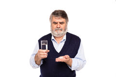 Old man with glass of water and pills in hands Royalty Free Stock Photography