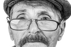 The old man in glasses. The face of an old man wearing glasses and a cap Royalty Free Stock Photography