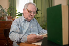 Old man in glasses reading a books in the room Stock Photography