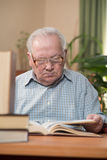 Old man in glasses reading a books in the room Stock Images