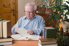 Old man in glasses reading a books in the room Royalty Free Stock Photo