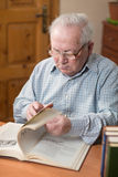 Old man in glasses reading a books in the room Royalty Free Stock Photos