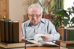 Old man in glasses reading a books in the room Royalty Free Stock Image
