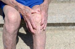 Old man with gnarled hands clutching his knee Royalty Free Stock Photo