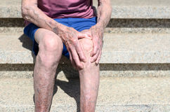 Old man with gnarled hands clutching his knee Royalty Free Stock Images