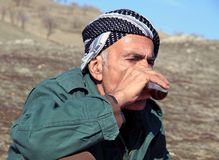 An old man. Is going out when he's climbing the mountains to have a picnic in a village near qaladiza town, he's drinking kurdish tea stock images