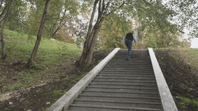 Old man is going up the stairs in park stock footage