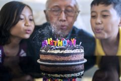 Old man and grandchildren blow birthday candles royalty free stock photo