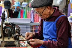 The old man granding keys in yuantong town in sichuan,china Royalty Free Stock Images