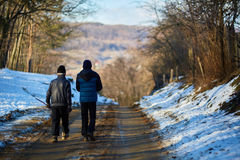 Old man and grandson walking in the countryside Stock Photos