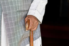 Old man hand on his walking stick. Elderly man walking with the support of wooden walking stick  with copy space Stock Photos