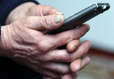 Old man hand holding remote control, selective focus Royalty Free Stock Photos
