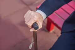 Old man hand holding walking stick outdoor royalty free stock photo