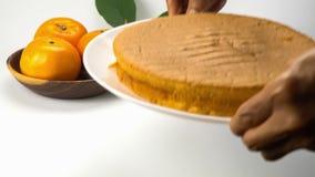 Old man hand putting a white ceramic dish of homemade lemon orange sponge cake on a white table.