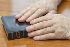 Old man hands on bible Royalty Free Stock Photography