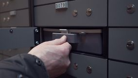 Old man hands puts plastic case inside bank safe depository cell stock footage