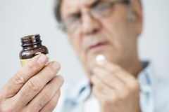 Old man taking a pill. Old man hands taking a pill royalty free stock images