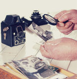 Old man hands, view photos with magnifying glass from the past, retro cameras on the table, filtered Royalty Free Stock Image
