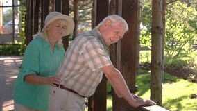 Old man has backache. Elderly couple outdoors. Pains in lower back. Old traumas influence health stock video footage