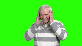 Old man has a headache. Grandpa regretting about something. Green hromakey background stock video footage