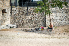 Old man having beer. Ouranoupoli, Greece - September 13, 2016: Old man is having beer near the tower in Ouranoupoli, Athos peninsula in Halkidiki, Greece royalty free stock photo