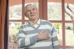 Old man having chest pain. stock image