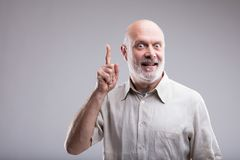 Old man having a great BIG idea. This old bald man had a brilliant idea that could make him reach or successful Stock Image