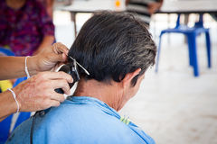 Old man having a haircut with a hair clippers Royalty Free Stock Images