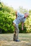 Old man having lumbago pain. While walking in the park Royalty Free Stock Photo