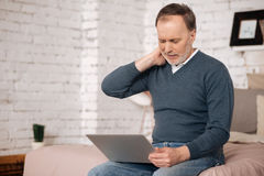 Old man having neckache while using laptop Royalty Free Stock Image
