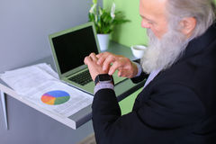 Old man head leader completes working day, sitting at laptop at. Senior publishes latest phrases on computer and introduces amendments to business plan and Stock Photography