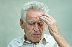 Old man with headache. Elderly man with hand on his temple has a headache Stock Photo