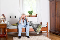 Old man with headache. Old man sitting on bed and holding head with hands royalty free stock photos