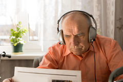 Old Man with Headset Reading Newspaper Stock Image
