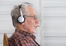 Old man with headset Royalty Free Stock Image