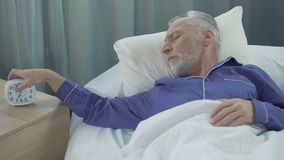 Old man hearing alarm clock, reluctant to wake up, lack of sleep and energy. Stock footage stock footage