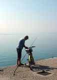 Old man with his bike and fishing with rod. Elderly man parks his bike and gets ready to angle on concrete pier in Akcay, Turkey Royalty Free Stock Photo